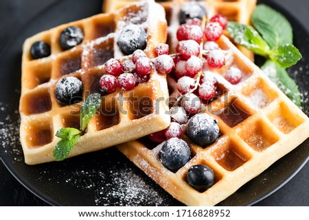 Square belgian waffles with berries and icing sugar on a black plate. Tasty sweet sugary waffles Stock fotó ©