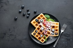 Square belgian waffles with berries and icing sugar on black plate, black background with copy space. Table top view sugar dessert on plate