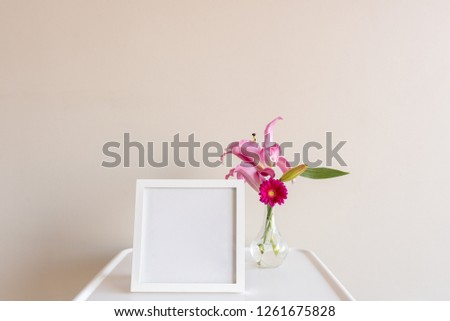 Square blank picture frame next to vase with pink gerberas and lilies on small white table against neutral wall background