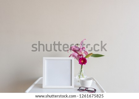 Square blank picture frame next to vase with pink gerberas and lilies on small white table with cup and glasses against neutral wall background