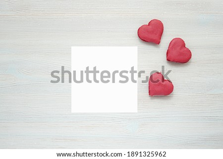 Photo of  Square card mockup, empty Valentines day greeting card and heart shape cookies, top view, love, romantic concept.