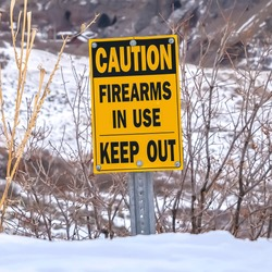 Square Caution Firearms In Use Keep Out sign on a mountain covered with snow in winter