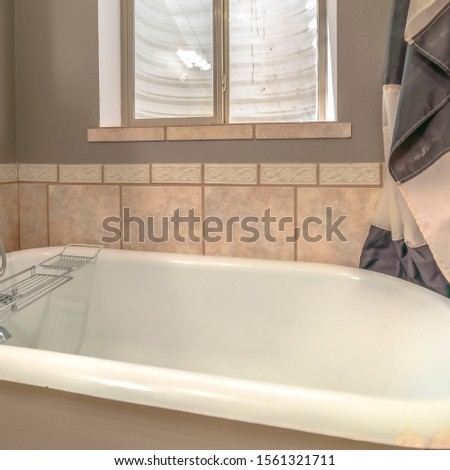 Square Close up of a bathtub in side a bathroom with shower curtains and window #1561321711