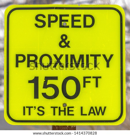 Square Close up of a bright yellow Speed and Proximity road sign with arrow #1414370828