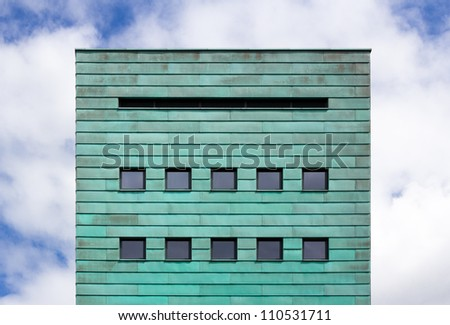 square facade with copper strips against cloudy sky