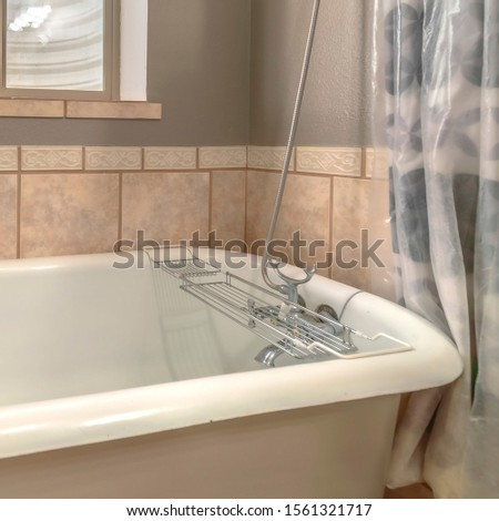 Square frame Close up of a bathtub in side a bathroom with shower curtains and window #1561321717