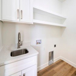 Square frame Empty white laundry room with top storage, laundry connections and dryer vent on the wall
