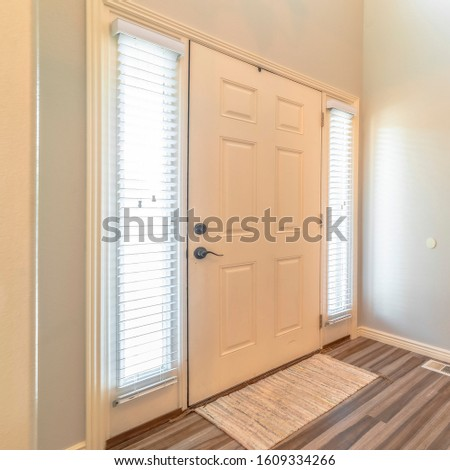 Square frame Home interior with stairs in front of the white front door flanked by sidelights