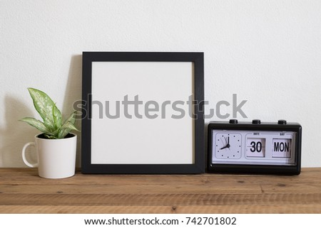 square frame photo with plant and clock on wooden table.home decor.happy morning time