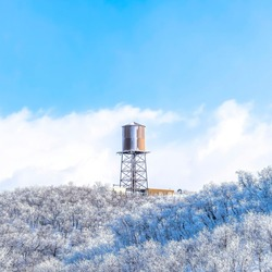 Square frame Wasatch Mountains landscape with water tank tower on the snowy slope in winter