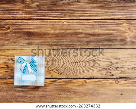 Square Gift Box Wrapped in Blue Plaid Paper with Blue and White Bow on Wooden Background with Copy Space seen from Above