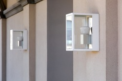 square hinged lantern on the wall in an iron case with a glass and a white lamp.