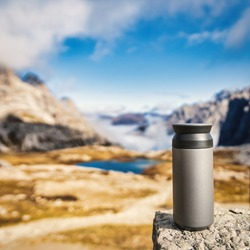 Square image of thermo cup standing on the rock with a view in Dolomites, Italy. Travel and adventure concept.