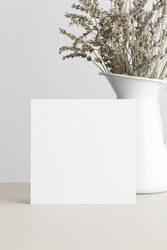 Square invitation card mockup with a dried lavender on a beige table.
