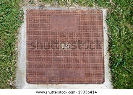 Square metal sewer hatch with light rust on the concrete man-hole in the middle of green grass