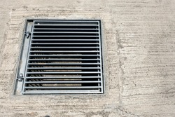 Square metal storm drain grill cover seen alongside a concrete walkway.