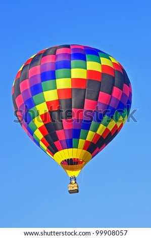 Square multicolored hot air balloon in a clear sky