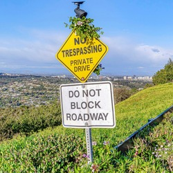 Square No Trespassing and Do Not Block Driveway sign at a private road in San Diego CA. Scenic view of the coastline and ocean under blue sky can be seen in the background.