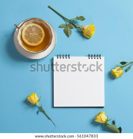Square notepad on springs with white kraft paper, yellow rose and cup of tea are on a blue background. Copy space
