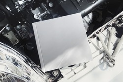 Square owner's manual book on a car engine mockup.