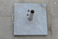 Square parasol holder that will protect person against sun. A grey block that will hold the parasol placed on the pavement. Mostly used in summer for a stable parasol.