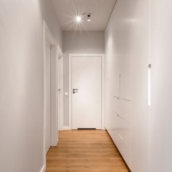 Square photo of long home corridor with doors and wardrobe