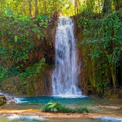 Square photograph of a waterfall in the Agua Azul Cascades in the Chiapas state rainforest near Palenque, Mexico.