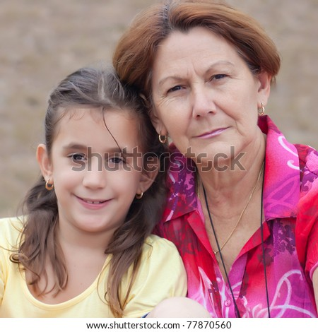 Square portrait of a cute latin girl and her grandmother with a diffused grass background
