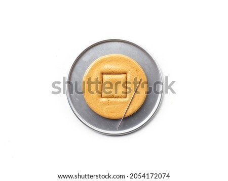 Square shaped Korean Dalgona or Ppopgi honeycomb candy with needle to play Squid Game challenge on white background