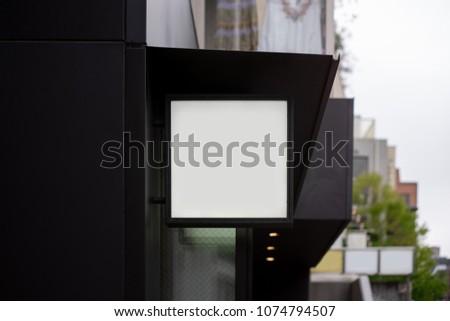 Square signboard shop Mock up on black building #1074794507