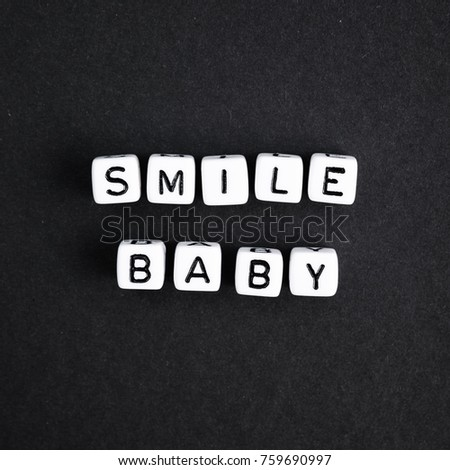 Square smile baby phrase made of white beads on black background.  a series of minimalism phrases and words. #759690997