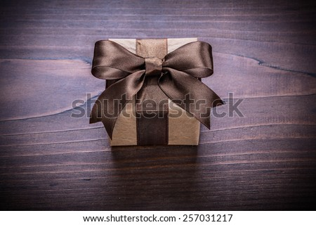 square vintage gift box with brown ribbon on old wooden board holiday concept
