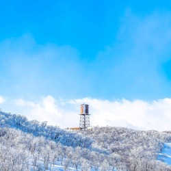 Square Wasatch Mountains landscape with water tank tower on the snowy slope in winter