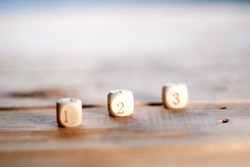 Square wooden dice with numbers on a wooden table,number on toy concept
