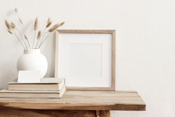 Square wooden frame mockup on vintage bench, table. Modern white ceramic vase with dry grass, books and busines card. White wall background. Scandinavian interior.