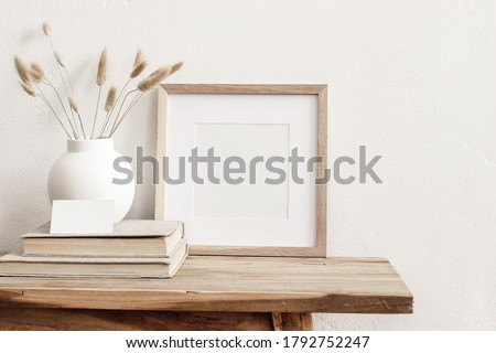 Photo of  Square wooden frame mockup on vintage bench, table. Modern white ceramic vase with dry grass, books and busines card. White wall background. Scandinavian interior.