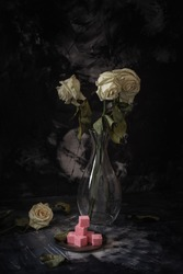Squared pieces of rose colored sweets lying on small steel plate, three faded roses in glass vase and one rose on the table, dark background