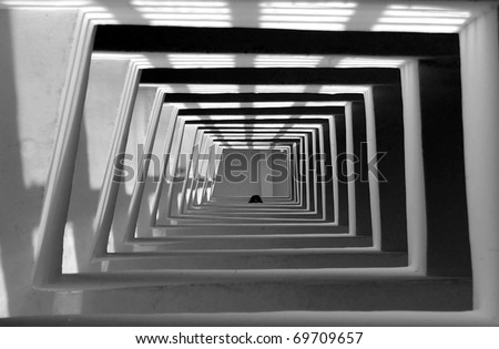 Squared stair shaft of tall building with someone looking down