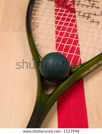 Squash ball and racket next to a red line