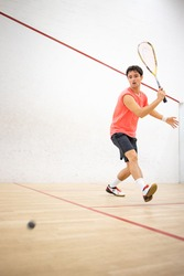 Squash player in action on a squash court (motion blurred image; color toned image)