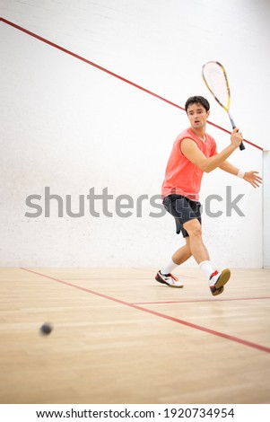 Squash player in action on a squash court (motion blurred image; color toned image) Сток-фото ©