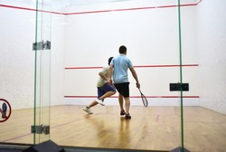 Squash player in action reaching on squash court. Squash Players on Tournament. Sports equipment and sportswear for playing squash. Soft focus