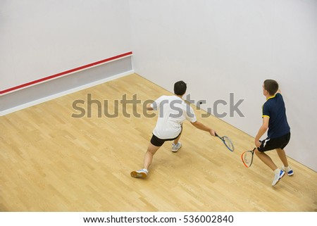Squash players in action on squash court, back view/Two men playing match of squash. Stock photo ©