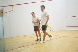 Squash players shaking hands after the game on squash court. Two men playing match of squash
