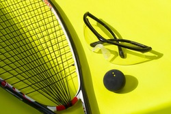 Squash racket, ball and glasses on a bright yellow background. Squash sport equipment in trendy style.