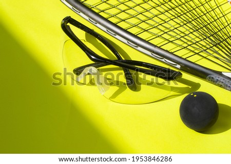 Squash racket, ball and glasses on a bright yellow background. Squash sport equipment in trendy style. Сток-фото ©