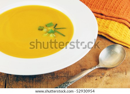 Squash soup  in white bowl with a spoon on a rustic wood table.