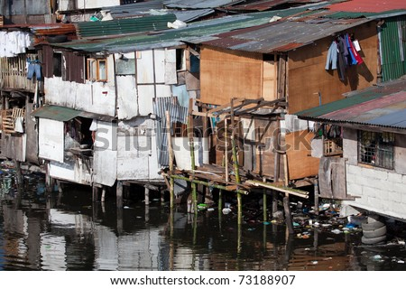 Squatter homes in the Philippines - shacks in shanty town along heavily polluted Paranaque river in Manila.