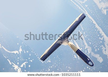 squeegee cleaning a soapy window, spring cleaning concept, blue sky with copy space