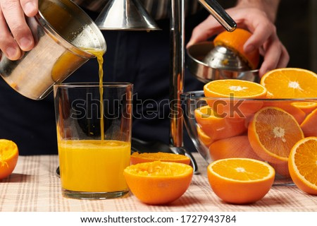 Squeezing an orange with a manual press, close view, making a glass of fresh. Fresh oranges on a wooden table, whole, squeezed and sliced. Foto d'archivio ©